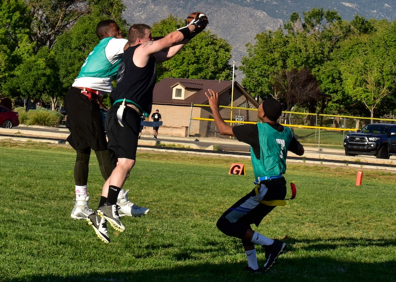 Tech. Sgt. Matthew Miller, safety for the 58th AMXS flag football team, intercepts a pass between two members of the WSSS-Joseph flag football team at Kirtland Air Force Base, N.M., Sept. 17, 2017. Each football game is split into two halves with each half lasting 20 minutes. (U.S. Air Force photo by Airman Austin J. Prisbrey)