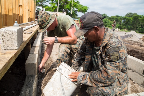 U.S. Marine Cpl. Randy O'Connell and a member of the Guatemalan Army Corps of Engineers work together to lay blocks at a construction site in Escuintla, Guatemala, July 19, 2018. The Marines, with Special Purpose Marine Air-Ground Task Force - Southern Command, are working with the Guatemalan military as part of a U.S. Southern Command humanitarian assistance project coordinated with the government of Guatemala to build temporary housing for people left without homes after Volcan de Fuego erupted in early June. The Marines and sailors of SPMAGTF-SC are conducting security cooperation training and engineering projects alongside partner nation military forces in Central and South America. The unit is also on standby to provide humanitarian assistance and disaster relief in the event of a hurricane or other emergency in the region. O'Connell, a native of Battle Creek, Michigan, is a water support technician with Marine Detachment - Southern Partnership Station, attached to SPMAGTF-SC.  (U.S. Marine Corps photo by Gunnery Sgt. Zachary Dyer)