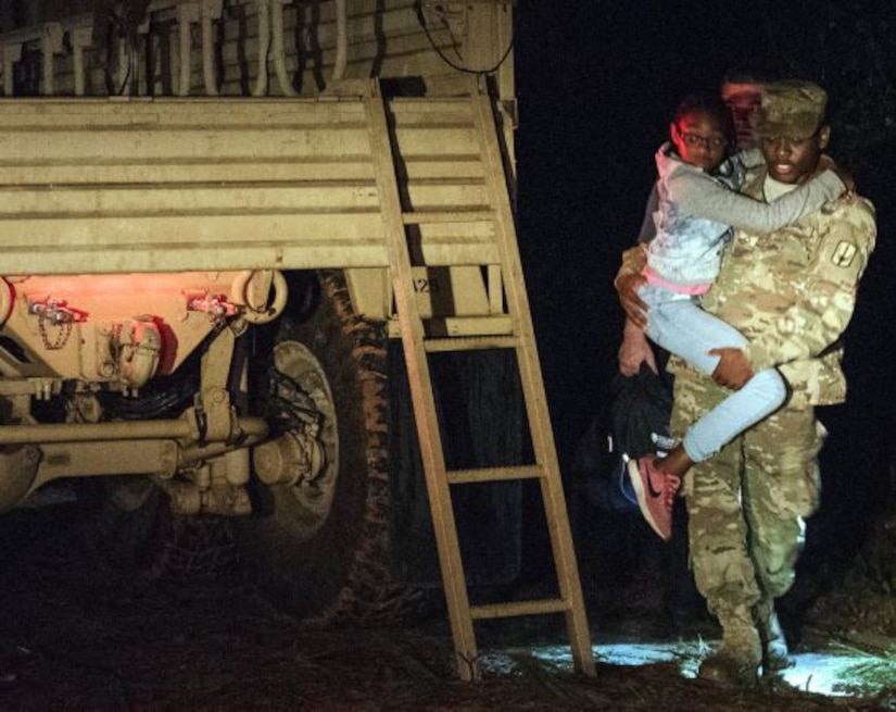 South Carolina Army National Guard Soldiers with the 1053rd Transportation Company assist a family that was trapped inside their vehicle during the early morning hours as a result of flood waters on the roadway in Hamer, S.C., Sept. 18, 2018. Rescues are underway in hard-hit North Carolina as well.