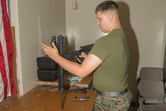 Lance Cpl. Joey Rhodes inspects a M16 A4 service rifle Aug. 9, 2018 at the Camp Foster armory, Okinawa, Japan.