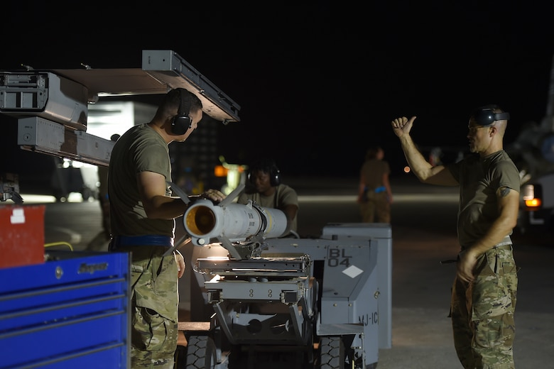 Airmen work on the flightline at night