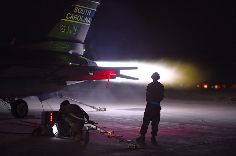 An  F-16 Fighting Falcon performs and afterburner run on the flightline at night