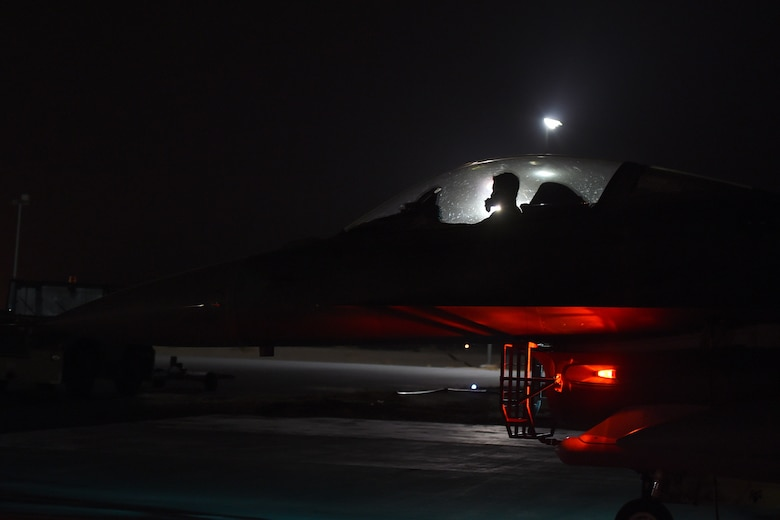An Airmen sits in the cockpit if and F-16 Fighting Falcon on the flightline at night