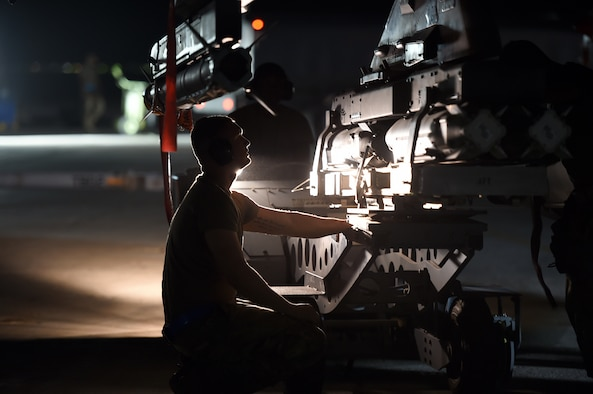 An Airmen works on the flightline at night