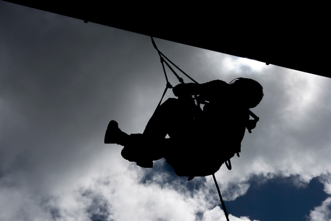 A firefighter trainee hangs from a line during rappelling training Sept. 14, 2018, at Kadena Air Base, Japan. The training aimed to instill a sense of trust in each member for their fellow firefighters, their equipment and their own abilities.