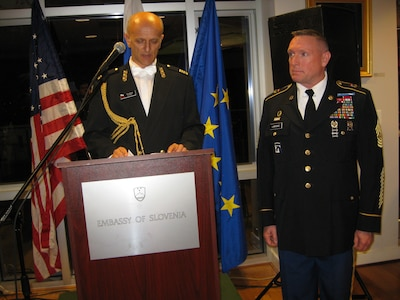 Slovenian Defense Attaché Col.  Ivan Mikuz awards Colorado National Guard Senior Enlisted Leader Command Sgt. Maj. Michael R. Lawrence the medal for multinational cooperation at the Embassy of the Republic of Slovenia June 23, 2015.  Lawrence has spent two decades helping build the partnership between Slovenia and Colorado as part of the National Guard State Partnership Program. (U.S. Air Force photo by Maj. Elena O'Bryan/Released)