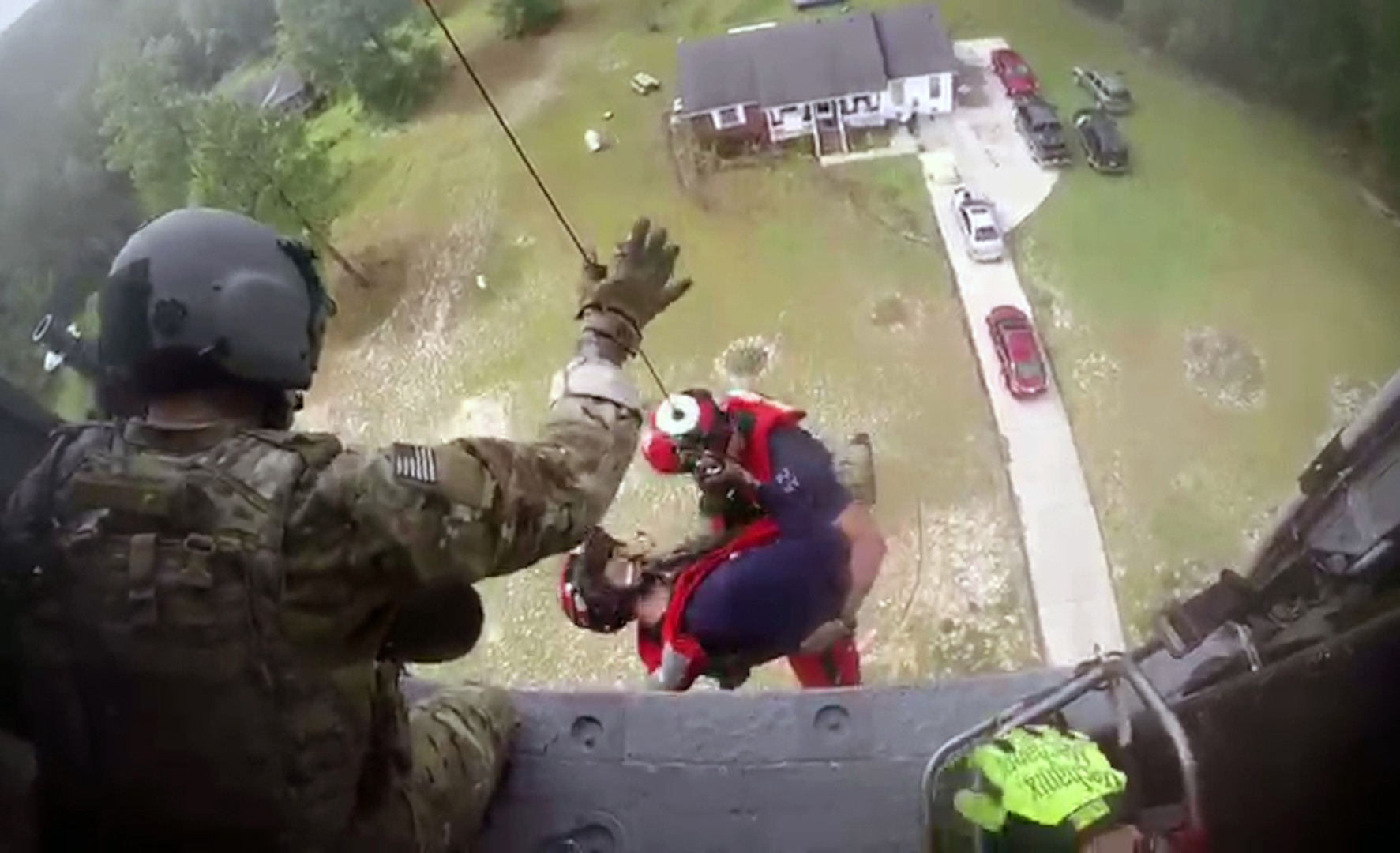 Pararescue Airmen Tech Sgt. Ryan Dush and Staff Sgt. Griffin Elzey, both members of the New York Air National Guard's 106th Rescue Wing, are lowered out of a HH-60 Pave Hawk helicopter assigned to the wing during a rescue mission in Lumberton, North Carolina, on Sept. 17, 2018. The two Airmen were descending to make an assessment of how many people were in the house, surrounded by flood waters and the best way to get them out. Eventually 15 people were rescued by two HH-60s, one flown by New York Air Guardsmen and the other by an aircrew from the California Air National Guard's 129th Rescue Wing.