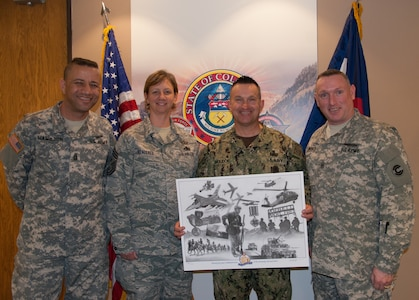 Command Sgt. Maj. Russell Hamilton, Chief Master Sgt. Annadele Kenderes, Fleet Master Chief Terrence I. Molidor, Command Sgt. Maj. Michael Lawrence, stand during a presentation of a print to Molidor on his introductory meeting with senior leaders of the Colorado National Guard in Centennial, Colorado Feb. 6, 2015. (U.S. Air Force photo by Tech. Sgt. Jecca Geffre/Released)