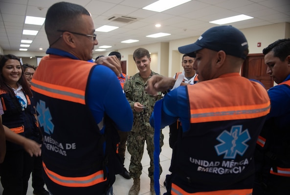 A U.S. Navy Sailor demonstrates proper tourniquet techniques with a Honduran emergency response medical professional.