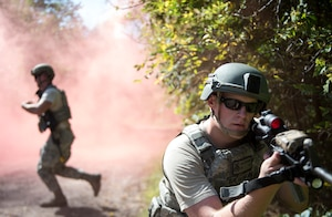 U.S. Air Force Staff Sgt. Zach Braegelmann, 133rd Security Forces Squadron, keeps a 360 degree perimeter as members cross the road at the Arden Hills Army Training Site, Arden Hills, Minn., Sept., 16, 2018.