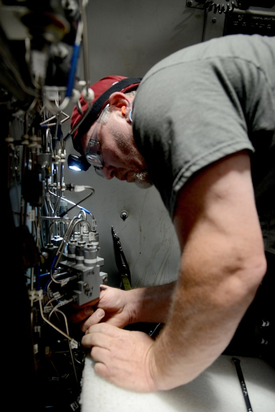Rod Weeks, an aircraft ordnance mechanic, inspects panel 4 of the defensive system operator section of a B-1B Lancer.