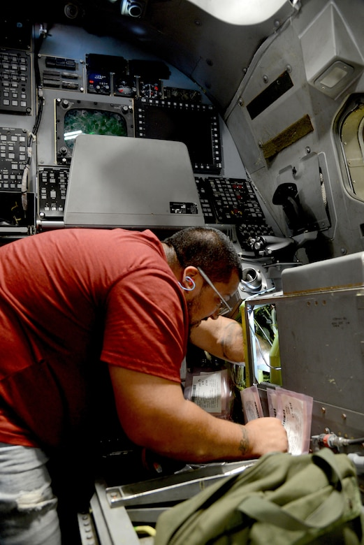 Ernesto Pena, an aircraft ordnance mechanic, works on the offensive system operator section of a B-1B Lancer.