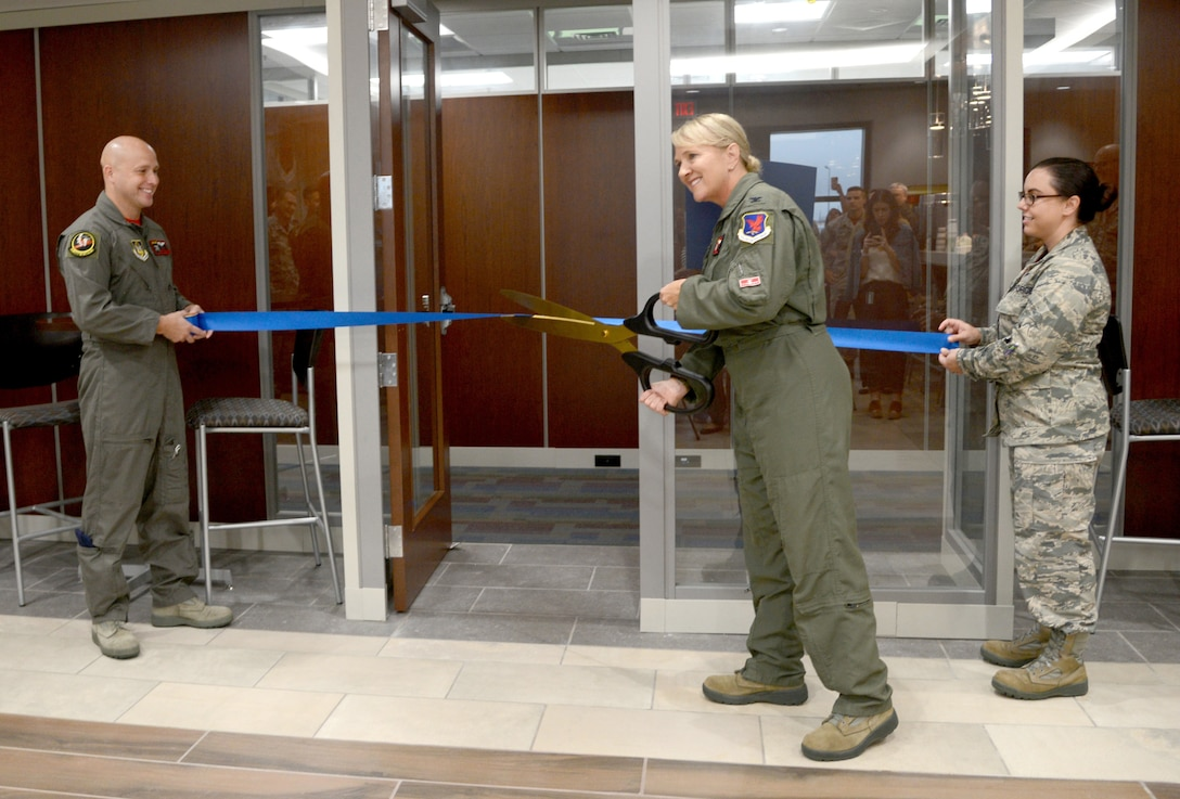 513th Air Control Group Commander Col. Laurie Dickson cuts the ceremonial ribbon inside Bldg. 461, the new home of the Thumpers. The 513th is a Reservist group which supports the 552nd Air Control Wing. The new 30,000 sq. ft. operations center will combine the 513ACG, the 513th Operations Support Flight (513OSS) and the 970th Airborne Air Control Squadron, after 20 years of being geographically separated on base.