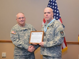 Lt. Gen. Richard P. Formica, commanding general, U.S. Army Space and Missile Defense Command/Army Forces Strategic Command, inducts Colorado Army National Guard Staff Sgt. Eugene A.K. Patton Jr., readiness noncommissioned officer, 117th Space Battalion, (1st Space Brigade), into the SMDC local chapter of the Sergeant Audie Murphy Club Feb. 27, 2013. (DOD photo by D.J. Montoya/Released)