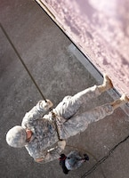 Sgt. Christopher Poquette, a multiple-launch rocket system crew member with the Colorado National Guard's Battery A, 3rd Battalion, 157th Field Artillery, rappels from a building in a training village at Fort Carson, Colo., Feb. 2, 2013. Eight Soldiers with the Colorado Army National Guard competed in the Best Warrior Competition Feb. 2 and 3, which included both night and day land navigation as well as oral boards, firing both rifles and handguns, and performance in a simulated city designed to offer everything from rappelling to medical evacuation. (Official Army National Guard photo by Sgt. Brandy Simmons/Released)