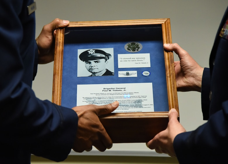 U.S. Air Force Lt. Col. Billy Wilson, 334th Training Squadron commander, presents Brig. Gen. Paul W. Tibbets IV, Air Force Global Strike Command deputy commander, Barksdale Air Force Base, Louisiana, with a shadow box during a room dedication ceremony at Cody Hall on Keesler Air Force Base, Mississippi, Sept. 14, 2018. The dedication honored Tibbets' grandfather, retired Brig. Gen. Paul W. Tibbets Jr., by dedicating the 334th Training Squadron Command and Control simulator in his name. Tibbets Jr., piloted the Enola Gay, which dropped the world's first atomic bomb. (U.S. Air Force photo by Kemberly Groue)