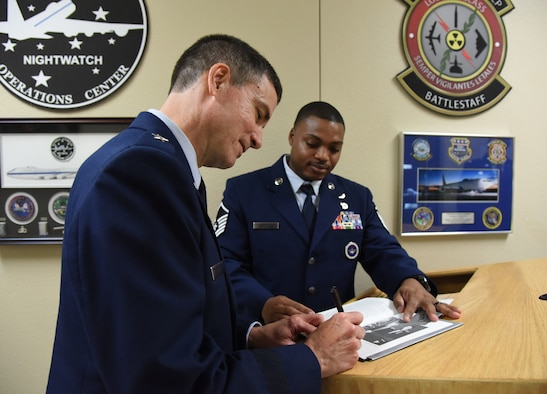 U.S. Air Force Brig. Gen. Paul W. Tibbets IV, Air Force Global Strike Command deputy commander, Barksdale Air Force Base, Louisiana, signs a book for Master Sgt. Sherman Roberts, 334th Training Squadron instructor, during a room dedication ceremony at Cody Hall on Keesler Air Force Base, Mississippi, Sept. 14, 2018. The dedication honored Tibbets' grandfather, retired Brig. Gen. Paul W. Tibbets Jr., by dedicating the 334th Training Squadron Command and Control simulator in his name. Tibbets Jr., piloted the Enola Gay, which dropped the world's first atomic bomb. (U.S. Air Force photo by Kemberly Groue)