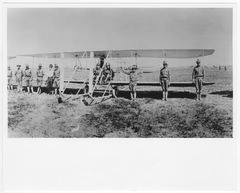 In the year of the 1st Aero Squadron's formation, Lt. Thomas D. Milling, instructor, and Lt. Fred Seydel, student, are at the controls of a Wright C., SC-16 Trainer on airfield in Texas City, Texas, May 1913. In front of the plane, 8 other soldiers in uniform and a civilian in white shirt and bow tie stand posed facing the camera. (U.S. Air Force Museum Courtesy photo)
