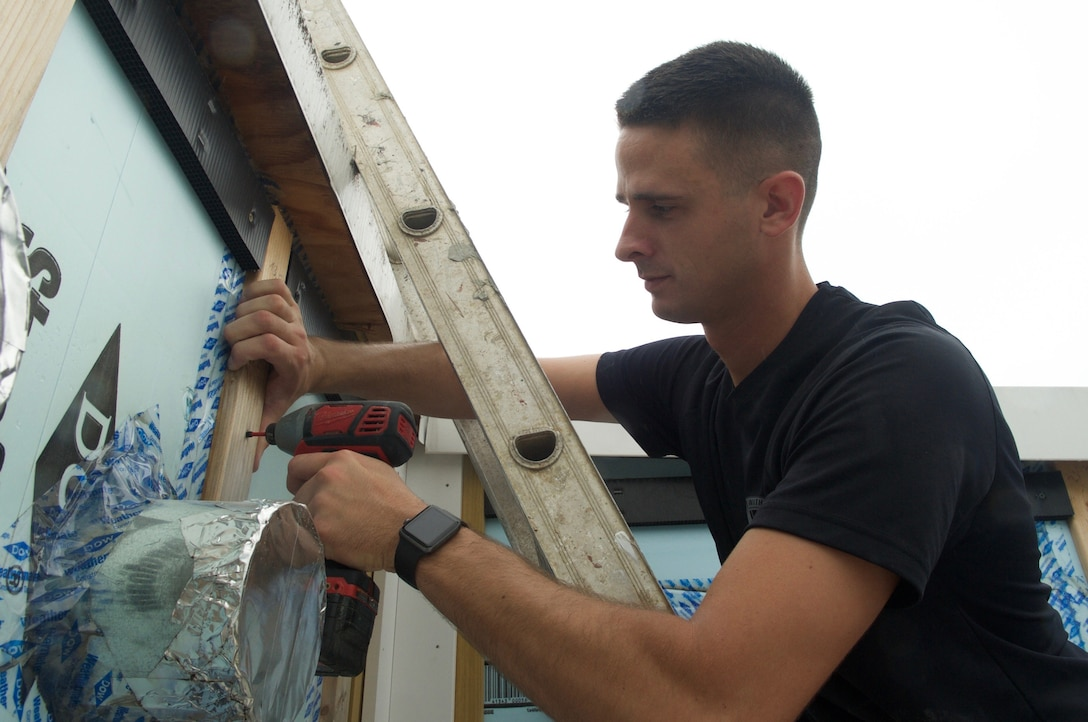 Air Force Senior Airman Daniel Eury Jr. drills a screw into a home he's helping to build with Habitat for Humanity in Washington, D.C.