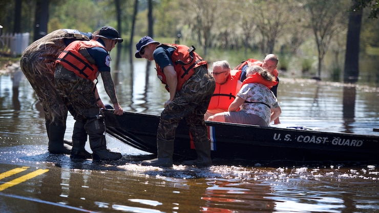 Members of the Coast Guard'rescue an elderly couple from floodwaters in a boat.