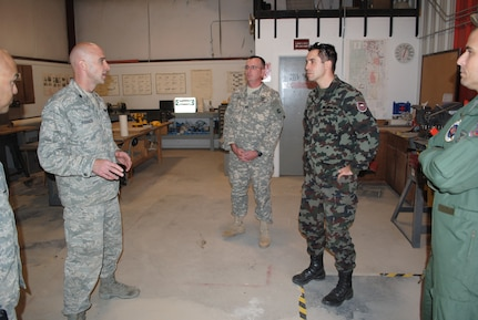 Lt. Col. John Stevenson, 140th Operation Support Squadron Airburst Range commander (left center) Stevens, Capt. Perry Read (center) and Slovenian armed Forces Sgt. 1st Class Darko Roth (right center) discuss training range management and how the Colorado Airmen manufacture their own training assets, such as targets, during a State Partnership Program visit to the 140th Operations Squadron's Airburst Range at Fort Carson, Colo., Oct. 31, 2012. The CONG and the Republic of Slovenia have been partner nations since 1993, when the program began. In addition to many other milestones in the program, Citizen-Soldiers from the CONG and soldiers from Slovenia have deployed together many times as members of the Operational Mentor Liaison Teams, now called Military Assistance Teams, to help train soldiers of the Afghan National Army. (Official Army National Guard photo by Officer Candidate Jennings Catlett/RELEASED)
