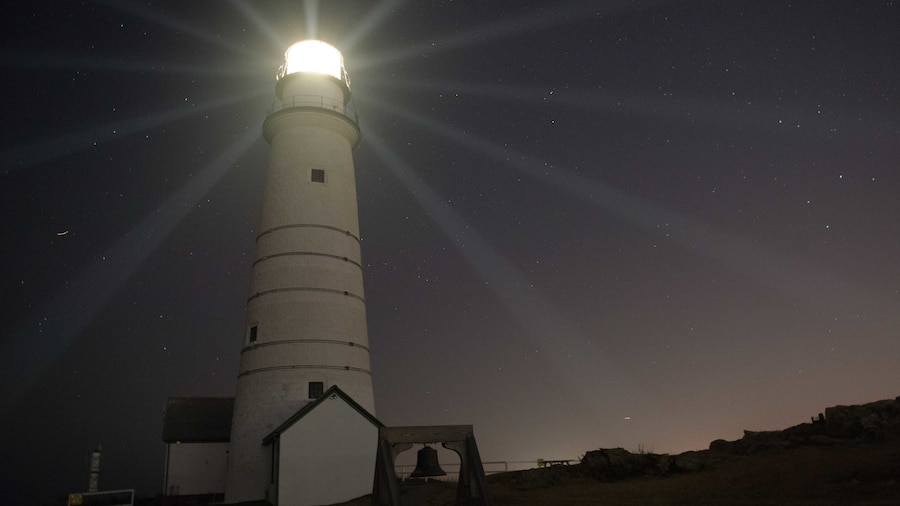 Beams of light emanate out on a dark gray sky from a white lighthouse.