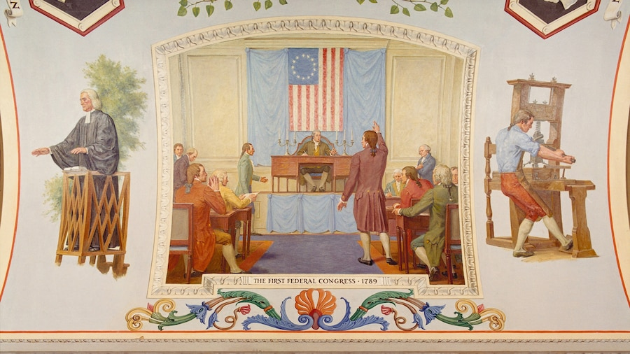 A painting shows a man in colonial garb standing and gesticulating in a room with seated men and an early U.S. flag adorning a wall.