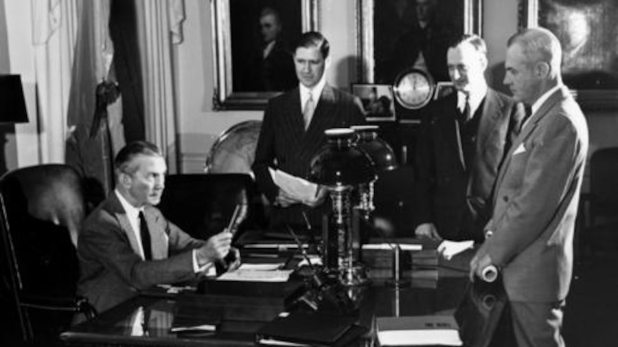 Three men stand around a desk where another man is seated.