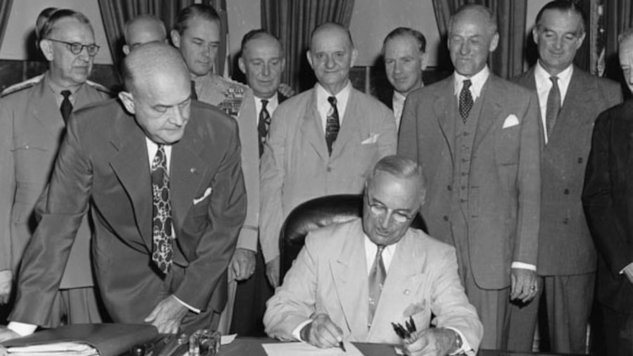 President Harry S. Truman signs a document at his desk in the Oval Office, as men stand around him and watch.
