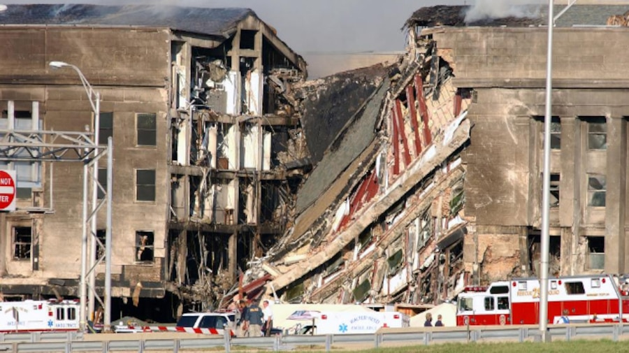 A destroyed section of a Pentagon facade is sandwiched by intact sections, with fire vehicles parked in front.