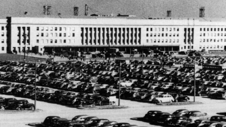 Cars sit parked in rows in a lot outside the Pentagon.