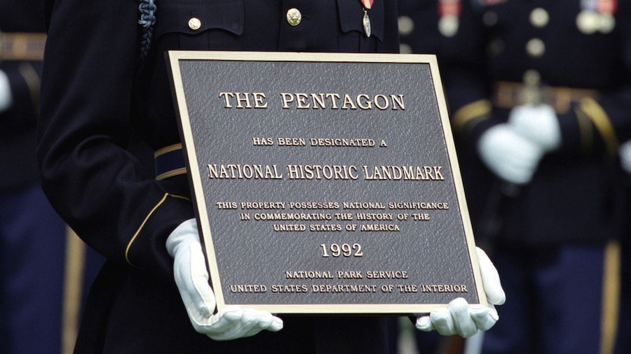 A soldier's white-gloved hands hold up a National Historic Landmark plaque for the Pentagon.