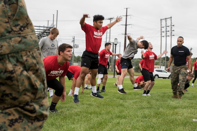 ST. CLOUD, Minn. -- The Marine Corps Officer Selection Team from Fargo, North Dakota, pushes the St. Cloud State University Wrestling team through a Leadership and Cohesion Exercise designed to test their physical and mental strength, as well as their ability to work as team, in St. Cloud, M.N., Sept. 18, 2018. At the end of the exercises, the Marines lead the team through a discussion about their core values; honor, courage and commitment, and how the athletes can apply those values to what they do as wrestlers, but also as students and ambassadors for the university.