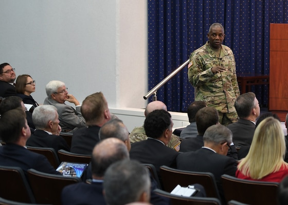 General in fatigues talking to seated audience