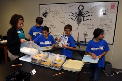 Children gather material to build a lasagna bridge, to learn about buoyancy, while attending STARBASE at Goodfellow Air Force Base, Texas, Sept 7, 2018. The students learned about buoyancy by creating a bridge with only marshmallows, popsicle sticks and lasagna, this gave a hands-on demonstration about weight distribution. (U.S. Air Force photo by Airman 1st Class Zachary Chapman/Released)