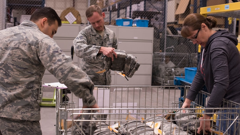 Airman Diego Najera-Dominguez, 92nd Logistics Readiness Squadron Individual Protective Equipment apprentice (left), Staff Sgt. Jeffery Jones, 92nd LRS Individual Protective Equipment supervisor, and Jessica Parker, 92nd LRS IPE Supply Technician supervisor, sort through Joint First Aid Kit packages Sept. 19, 2018, at Fairchild Air Force Base, Washington. Logistics Airmen are tasked with the organization, tracking and issuing of hundreds of thousands of individual pieces of gear for training and deployment purposes. (U.S. Air Force photo/Senior Airman Ryan Lackey)