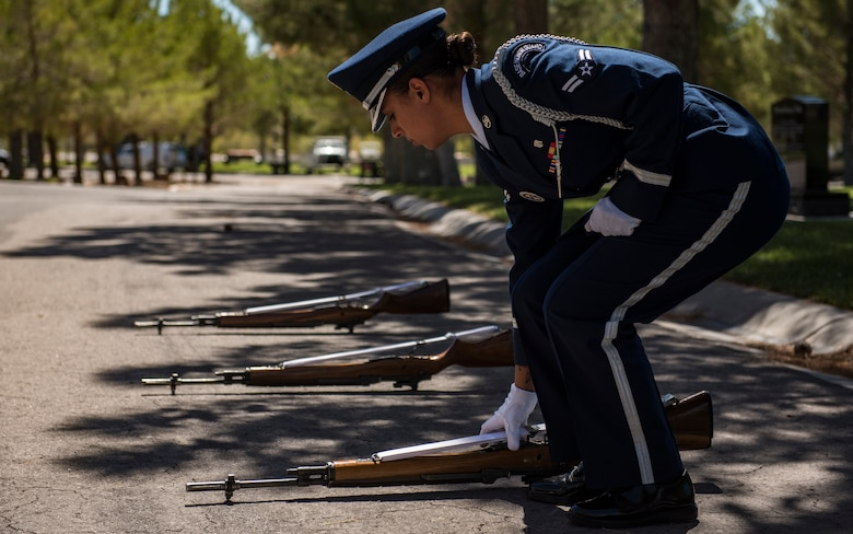 A1C Ashely Libbey, Nellis Air Force Base honor guardsman, aligns rifles during a military honors funeral at the Southern Nevada Veterans Memorial Cemetery, Sept. 14, 2018. Before any guardsman is put on a detail, they have nearly a month of training to learn the basic movements. Afterwards, they continue to meticulously work out the slightest imperfections. (U.S. Air Force photo by Airman 1st Class Andrew D. Sarver)