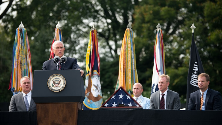 Vice President Mike Pence speaks at a lectern as Deputy Defense Secretary Patrick M. Shanahan looks on while seated on stage.