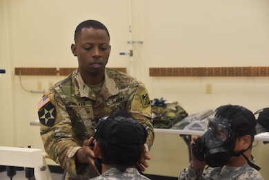 Capt. Courtney Walker, U.S. Army Corps of Engineers, Far East District operations officer, assists Emergency Essential Civilian (EEC) personnel with fitting their gas masks during the district's EEC training held at the Vehicle Maintenance Facility, Aug. 22.