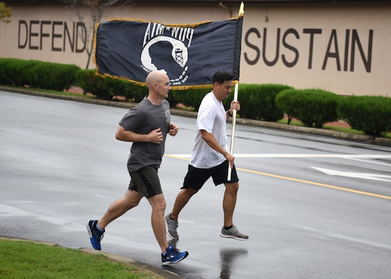 U.S. Air Force Tech. Sgt. Kurt Kanzler, a precision guidance munitions production supervisor with the 51st Munitions Squadron, runs with a prisoner of war and missing in action flag during a 24-hour vigil run at Osan Air Base, Republic of Korea, Sept. 21, 2018. The main purpose of POW/MIA Remembrance Day is to pay tribute and honor the sacrifices of prisoners of war and those who are missing in action. (U.S. Air Force photo by Staff Sgt. Sergio A. Gamboa)