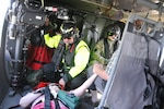 Flood victims hold hands aboard a UH-60 Black Hawk helicopter during an aerial evacuation over Marion County, South Carolina, Sept. 20, 2018. Pennsylvania Guard air crews joined to rescue them.