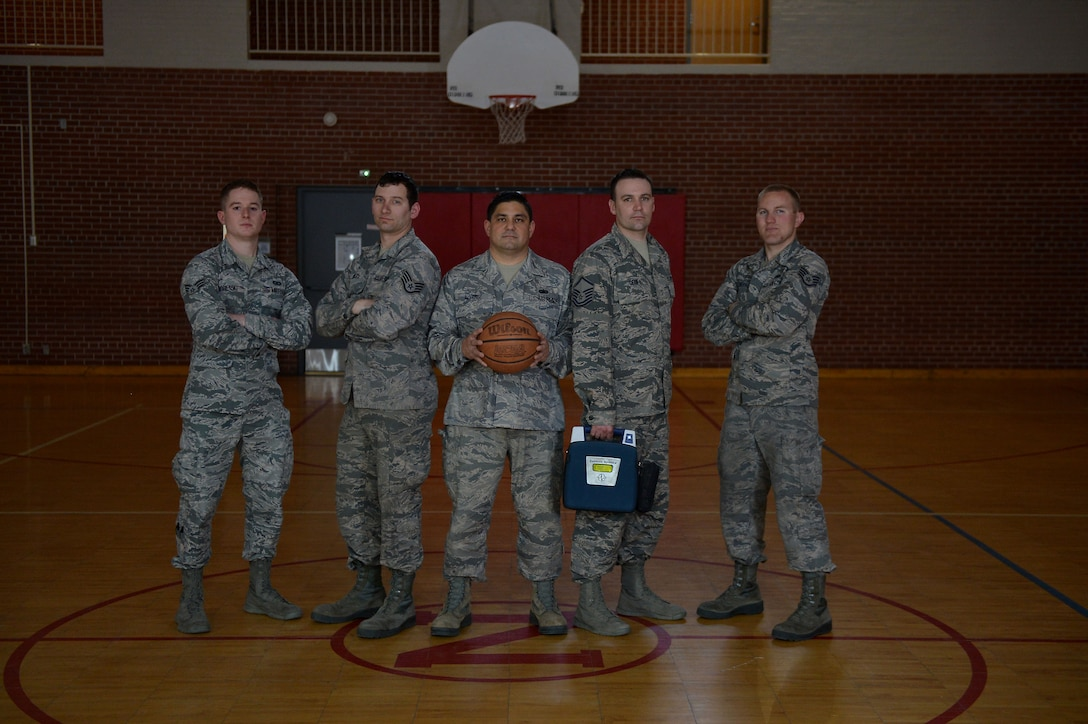 Senior Airman Jonathan Sobetski, Staff Sgt. Matthew Riley, Tech. Sgt. Michael Alvarez, Master Sgt. Jeremy Dean and Staff Sgt. Dan Schieffer pose on the basketball court right where the incident happened, April 17, 2018, at the Spirit of '76 Armory Lincoln, Nebraska. 