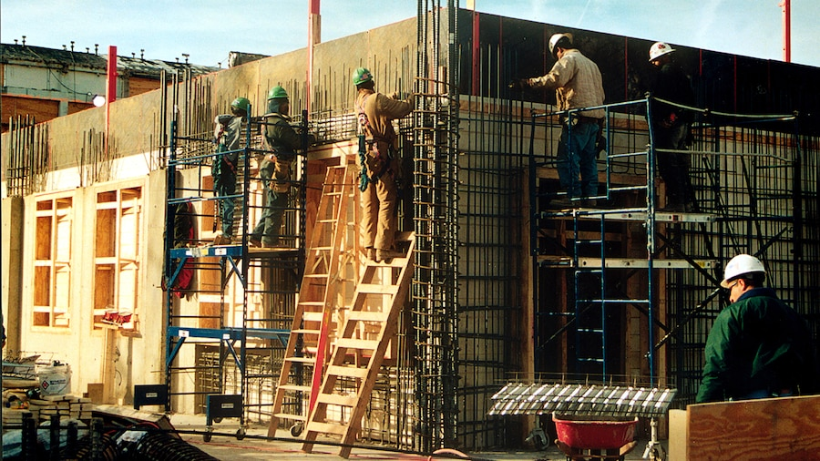 Construction personnel on ladders and scaffolding work with steel rods against a wood facade.
