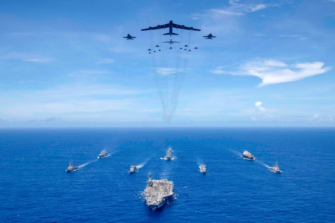 The aircraft carrier USS Ronald Reagan (CVN 76) leads a formation of Carrier Strike Group (CSG) 5 ships as Air Force B-52 Stratofortress aircraft and Navy F/A-18 Hornets pass overhead for a photo exercise during Valiant Shield 2018. The biennial, U.S.-only, field-training exercise focuses on integration of joint training among the Navy, Air Force and Marine Corps. (U.S. Navy photo by Mass Communication Specialist 3rd Class Erwin Miciano)