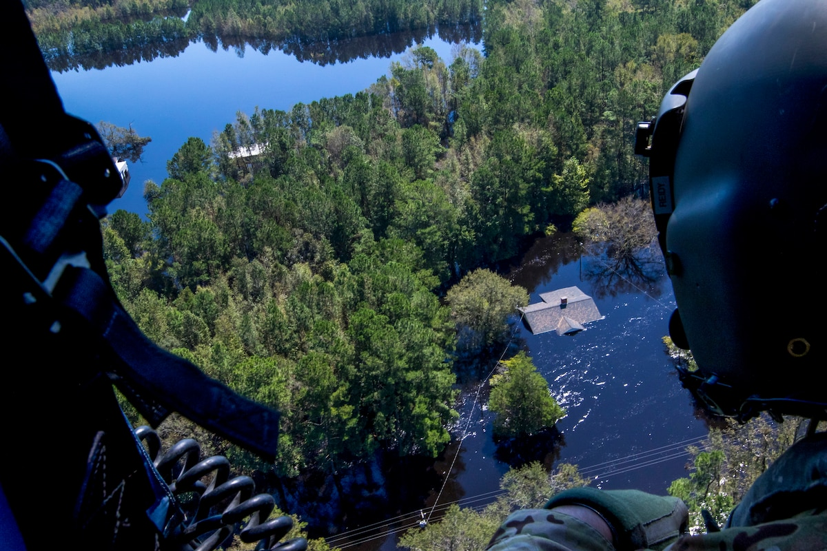A soldier looks out over a flooded area from a helicopter.