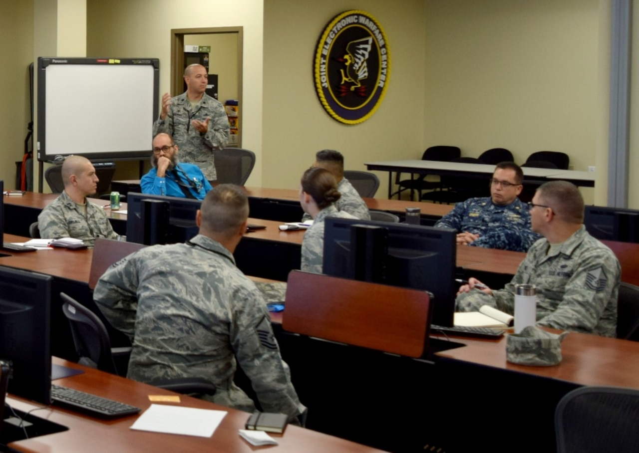 Military cyber experts meet in a conference room.