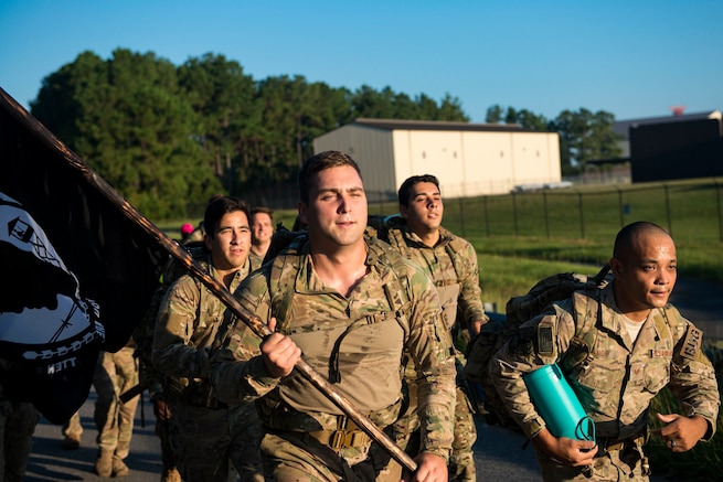 Airmen from the 822d Base Defense Squadron run during the POW/MIA Recognition Day ruck march, Sept. 21, 2018, at Moody Air Force Base, Ga. For the first-time, the 347th Operations Support Squadron hosted a ruck march to pay tribute to those who've been captured or missing in the line of duty by carrying a POW/MIA flag for 24 hours. (U.S. Air Force photo by Airman 1st Class Erick Requadt)