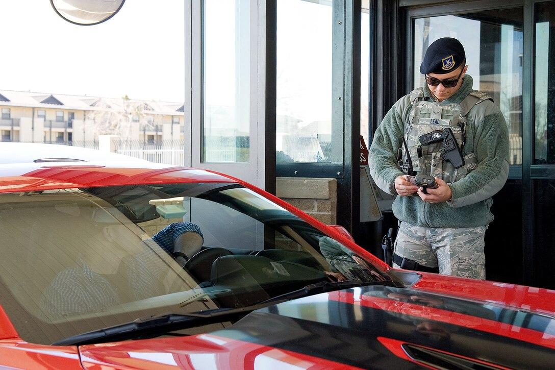 An airman checks an ID at a military base gate.