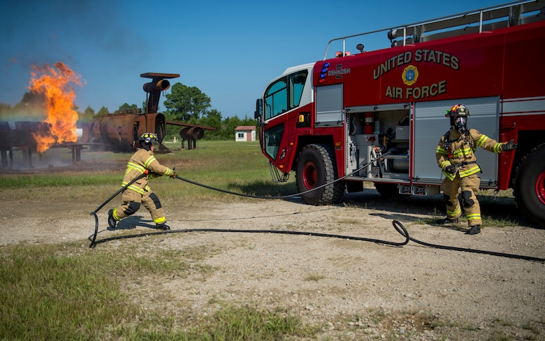 U.S. Air Force Airman 1st Class Todd Wagner, 633rd Civil Engineer Squadron firefighter and Staff Sgt. Isaac Sunnock, 633rd CES lead firefighter, participate in a live-fire training exercise at Joint Base Langley-Eustis, Virginia, Sept. 19, 2018.