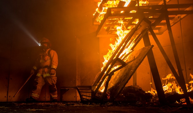U.S. Air Force Staff Sgt. Kyle Gregory, 633rd Civil Engineer Squadron lead firefighter, prepares a fire for a training exercise at Joint Base Langley-Eustis, Virginia, Sept. 20, 2018.